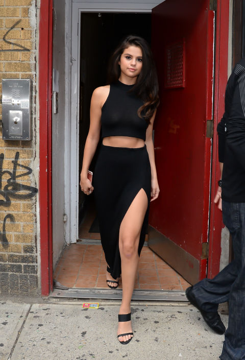 Selena looks super hot and sophisticated in a black crop top and black high-slit maxi skirt.