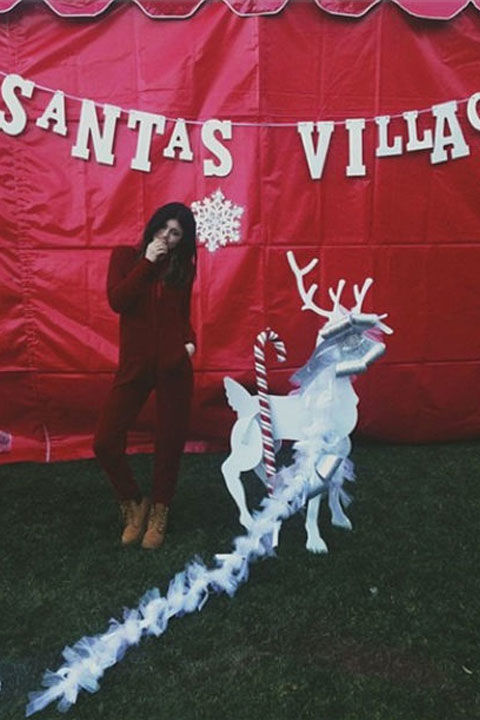 "Kylie wins the title for ""Cutest Santa's Little Helper"" in this adorable red onesie."
