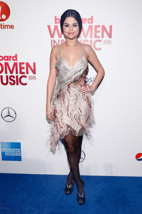 At the Billboard Women in Music Luncheon, Selena stood out in a feathered dress and black tights.