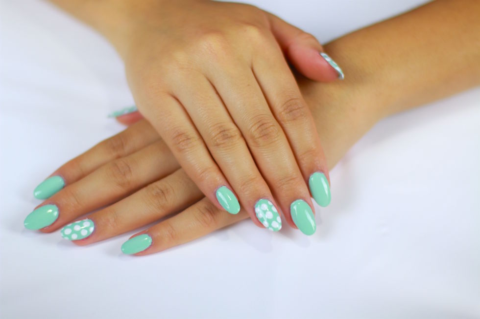 I love this design because it's super easy to achieve, which is comforting for beginners who are hesitant to decorate their own nails. Start off by applying a single coat of polish in your favorite color, then let it dry for a few minutes. Next, take a nail art tool, dip it into a contrasting shade and create a series of evenly spaced dots. Simple, right?