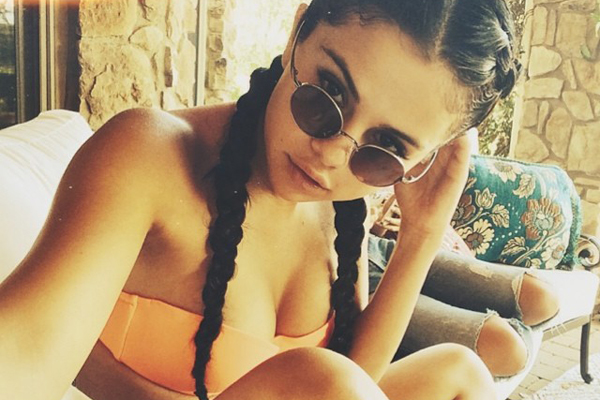 The summer-y color compliments Selena's complexion, while her hippie shades and braids add a funky twist to her simple bikini.