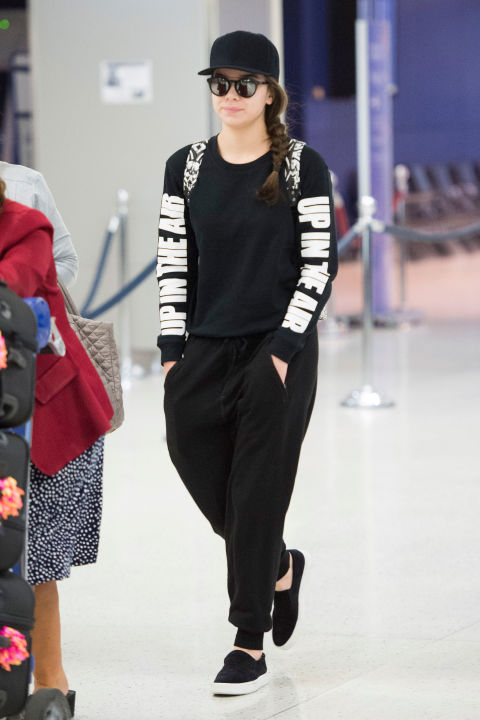 Hailee's cool snapback, slip-on sneakers, and backpack give her black sweats an urban edge.